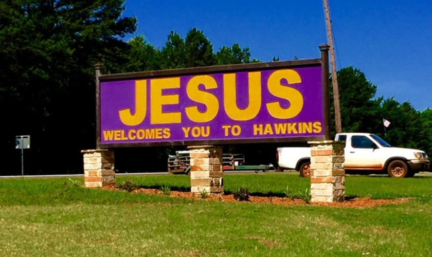 """Em tradução, na placa está inscrita a frase """"Jesus te dá boas-vindas à Hawkins""""."""