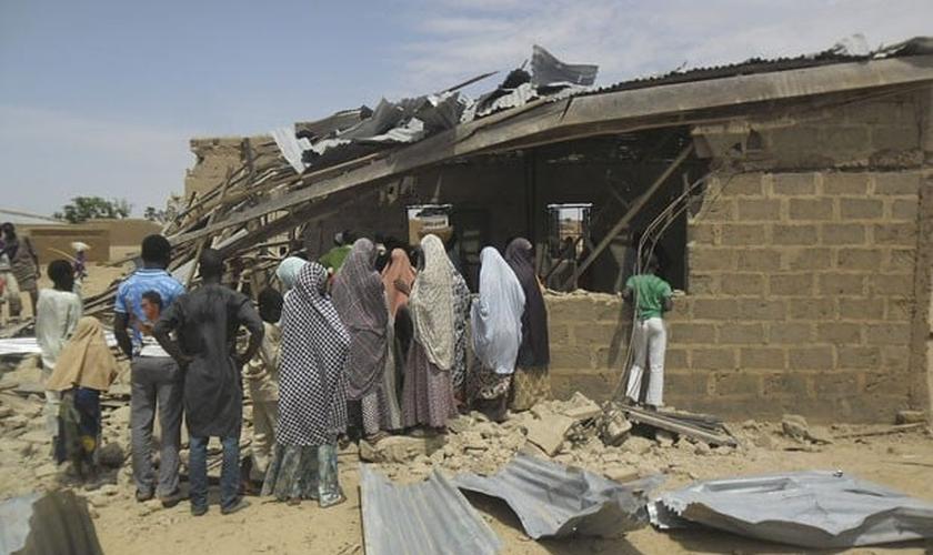 Pessoas são vistas ao redor de igreja que foi alvo de ataque suicida. (Foto: Adamu Adamu/AP)