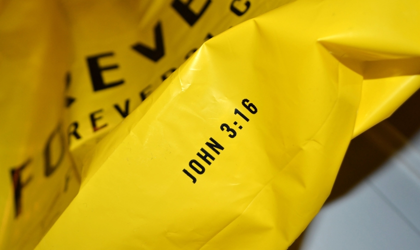 """Na sacola amarela da Forever 21 é impresso o texto """"John 3:16"""", em inglês, que significa João 3:16."""
