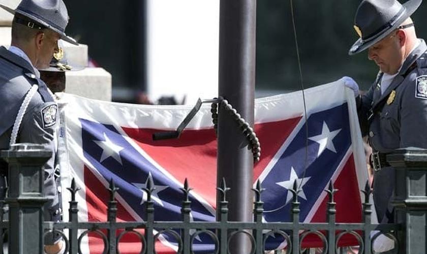 Guardas retiram bandeira confederada dos jardins do Capitólio. (AP Photo/John Bazemore)