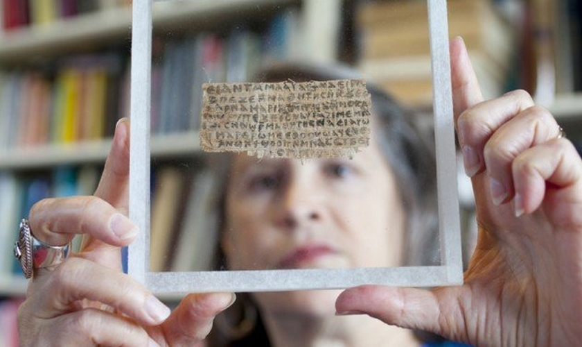 """Karen King exibe o papiro com trecho do """"Evangelho da Esposa de Jesus"""", desmascarado após revelação do antigo proprietário. (Foto: Harvard Magazine)"""