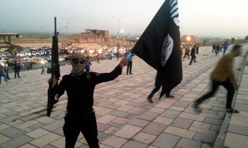 """Militante do Estado Islâmico levanta bandeira do grupo terrorista no Iraque, país onde as casas de cristãos foram marcadas com o mesmo sinal correspondente à letra 'N' do alfabeto ocidental, como sigla para a palavra """"nazareno"""" (Foto: Reuters)"""