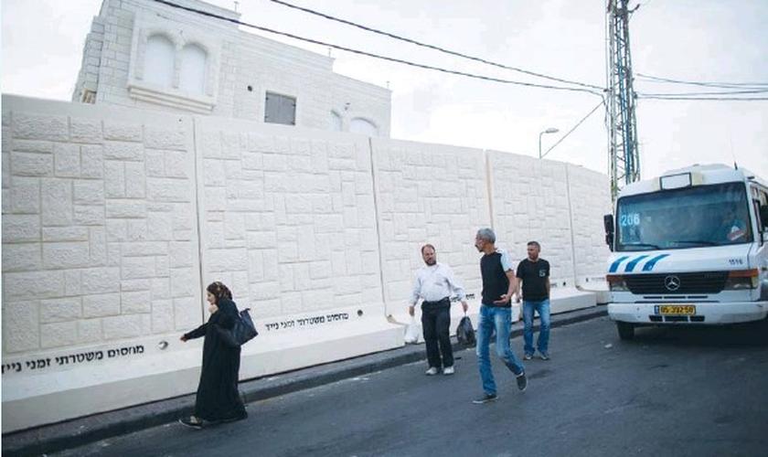 Palestinos caminham ao lado de um muro de concreto temporário no bairro Jabel Mukaber, erguido para proteger a vizinhança Armon Hanatziv de bombas e outros ataques terroristas. (Foto: Yonatan Sindel/Flash90)
