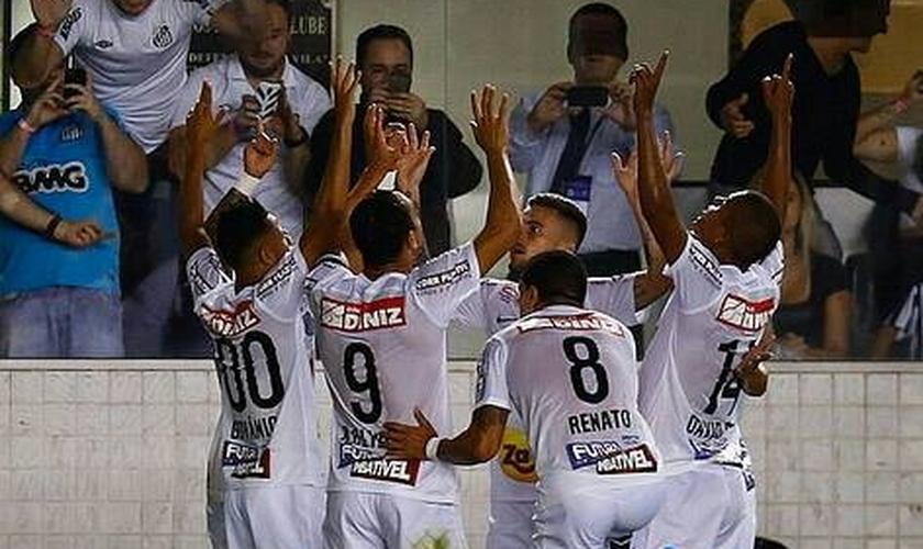 Ricardo Oliveira comemora gol com os companheiros de equipe, em atitude de gratidão a Deus.