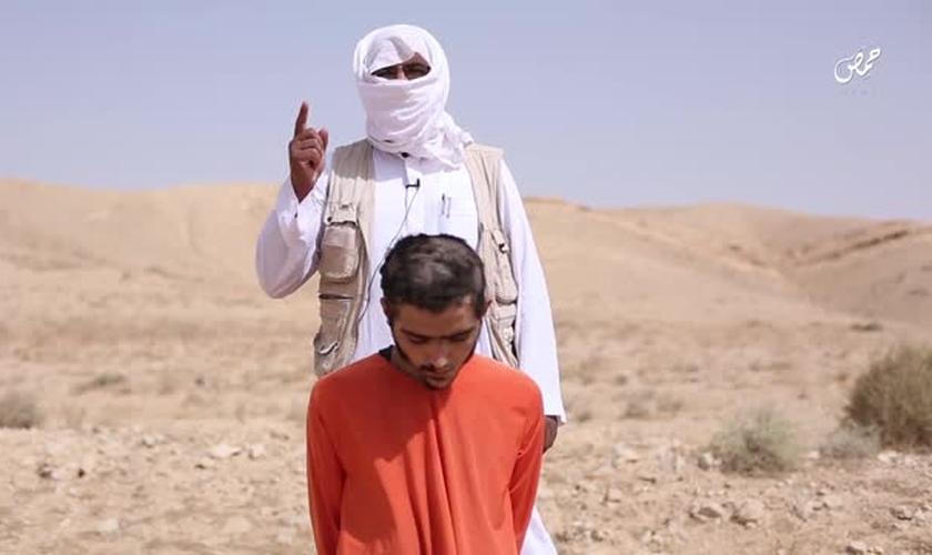 Um extremista do EI, vestido de branco, explica que sua morte é uma espécie de punição. (Foto: Heavy)