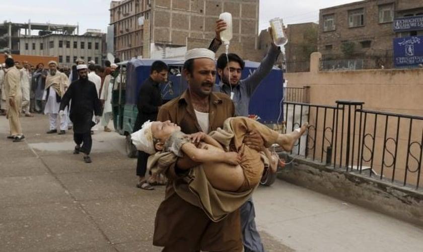 Homem carrega garoto ferido, após o terremoto, em Peshawar, no Paquistão (Foto: Reuters)