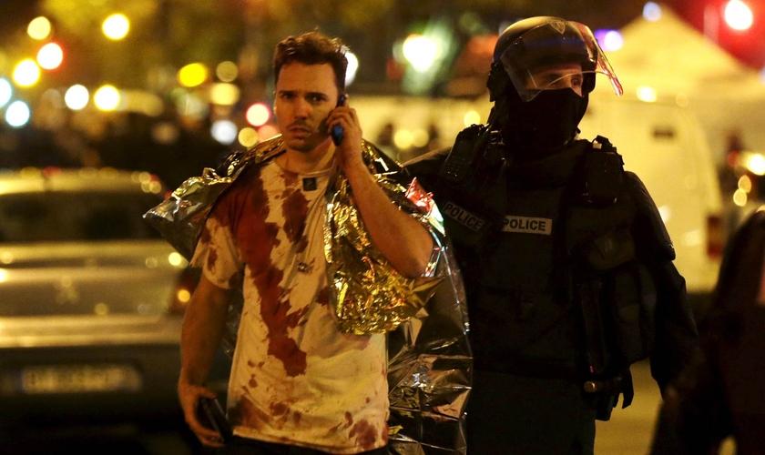 Policial acompanha vítima do ataque à casa de shows 'Bataclan', em Paris. (Foto: Reuters)