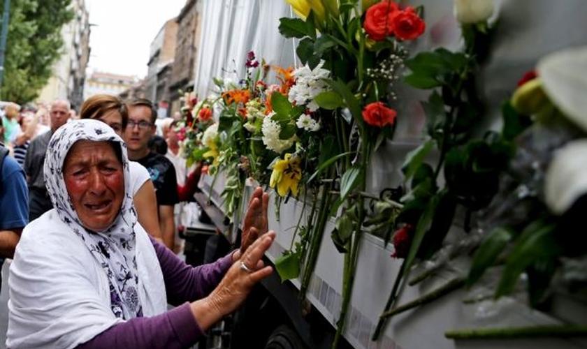 Uma mulher chora ao lado de um caminhão que transportava 136 caixões de recém-identificadas vítimas do massacre de Srebrenica, em 1.995 (Foto: Reuters)