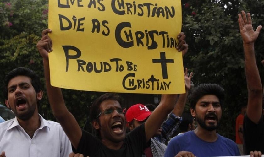 """Manifestante paquistanês segura cartaz com as frases: """"Viver como cristão! Morrer como cristão! Orgulho de ser cristão!"""". (Foto: Reuters)"""