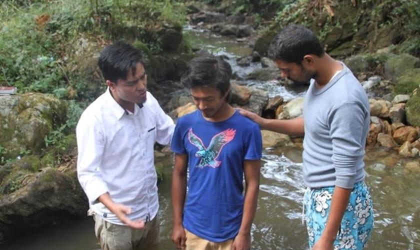 Pastor Lazrus e outro membro de sua equipe oram com jovem, antes de seu batismo, realizado em uma pequena cachoeira da região. (Foto: Levitas Nepal)