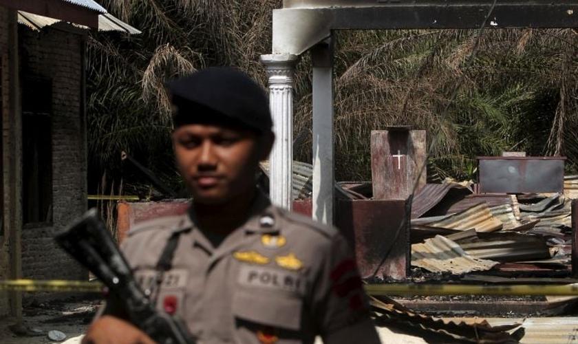 Policial segura rifle enquanto fica de guarda em frente a uma igreja queimada em Suka Makmur Village, em Aceh, Indonésia
