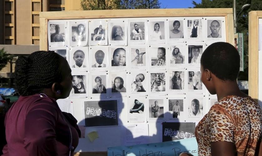 Pessoas olham um mural com fotos de alguns dos 150 estudantes assassinados na Universidade de Garissa, durante a trágica manhã de 02 de abril de 2015 (Foto: Reuters)