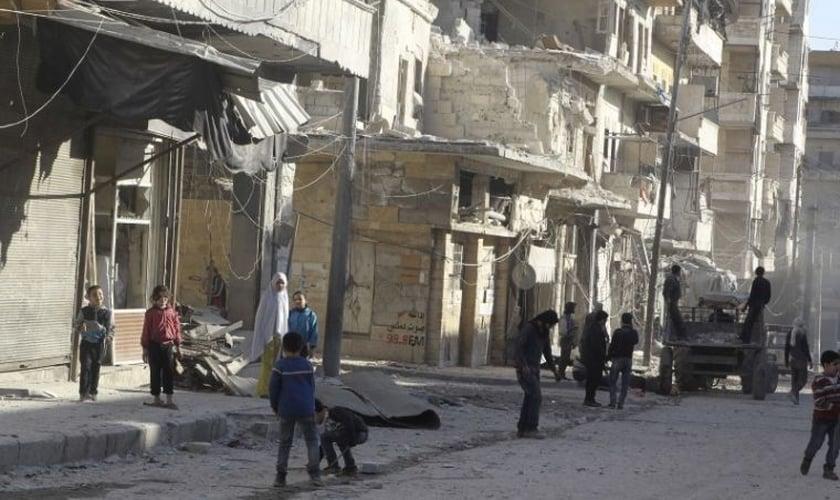 Moradores perto de edifícios danificados na vila de Kafr Hamra, no norte rural de Aleppo, Síria (27 de fevereiro de 2016). Foto: Reuters.