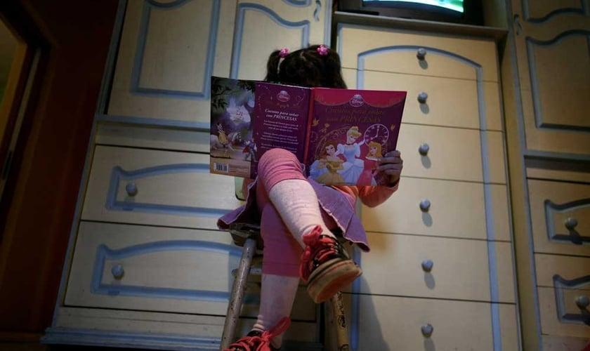 Lulu, uma 'menina' transgênero, lê um livro em seu quarto em sua casa em Buenos Aires. (Foto: Reuters)