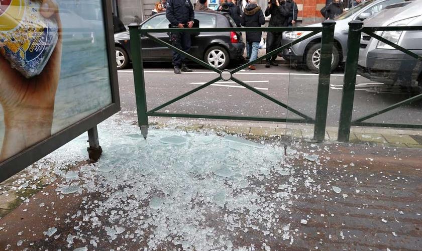 Policial olha para vidro quebrado no ponto de bonde, após a captura de suspeito de ataques em Bruxelas, enquanto a equipe de uma emissora local capta imagens. (Foto: Reuters)
