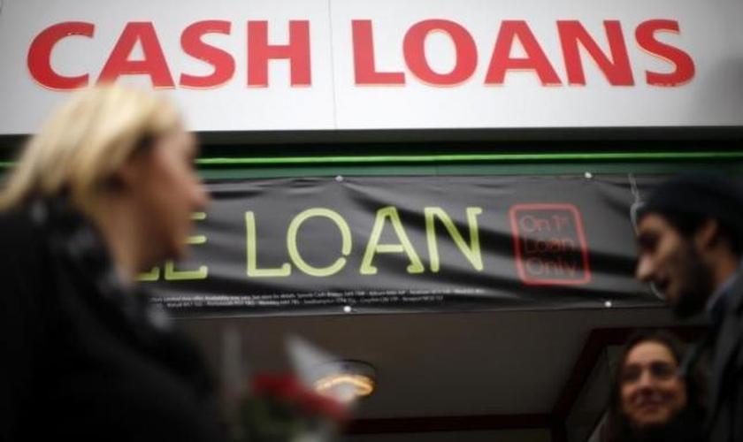 Pedestres passam em frente a empresa que faz empréstimos nos EUA (Foto: Reuters)