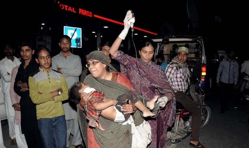 Mulher segura criança que ficou ferida em atentado em parque de Lahore. (Foto: Arif Ali/AFP)