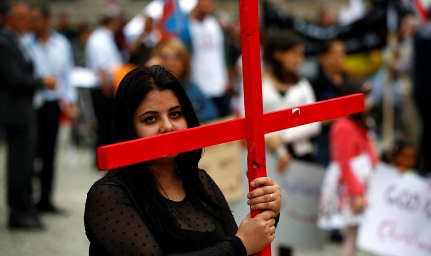 Mulher segura uma cruz durante protesto organizado por cristãos iraquianos na Alemanha. (Foto: Reuters / Thomas Peter)