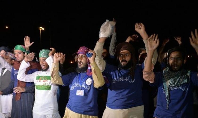 Muçulmanos gritam slogans contra o governo em frente ao prédio do parlamento. (Foto: Aamir Qureshi / AFP)