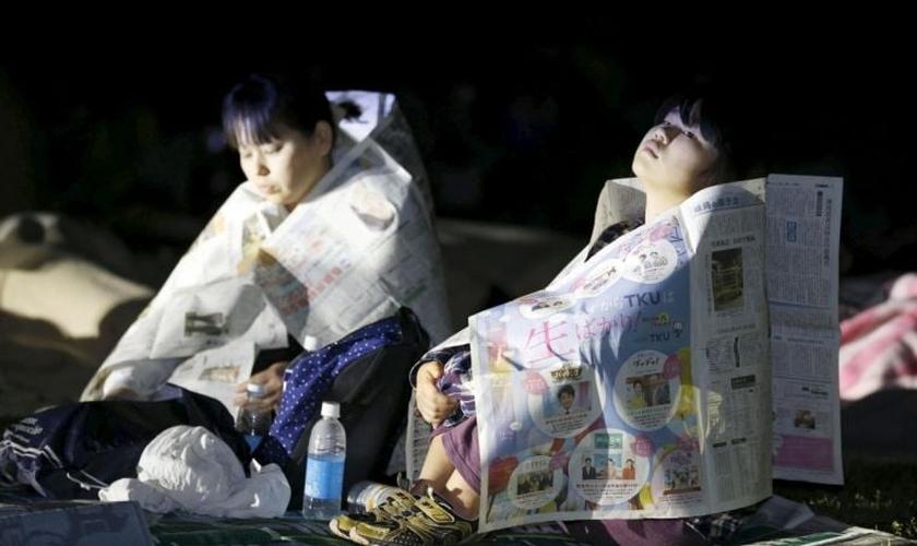 Sobreviventes do terremoto usam jornais para se aquecer, enquanto não são levadas pelas equipes de resgate. (Foto: Reuters)