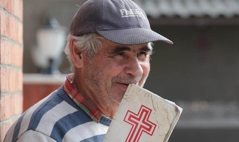 Cristão iraniano segura Bíblia nas mãos. (Foto: Sat 7)