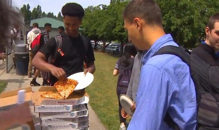 Estudante pega um pedaço de pizza grátis entregue pela igreja Bethany Community Church em Seattle, nos EUA. (Foto: Reprodução/Komo TV)