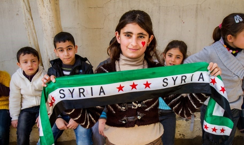 Garota síria posa com faixa inspirada na bandeira de seu país. (Foto: Crossmap)