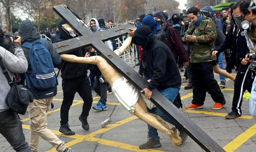Ao final da marcha, da última quinta-feira, manifestantes mascarados entraram em uma igreja no centro de Santiago e destruíram a cruz 3 de metros de altura, com uma estátua de Jesus Cristo. (Foto: Reuters)