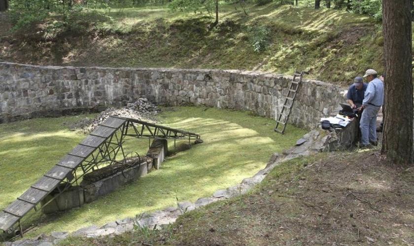 Pesquisadores num fosso usado para manter vítimas antes de sua execução, num campo de concentração da Lituânia. (Foto: Ezra Wolfinger/AP)