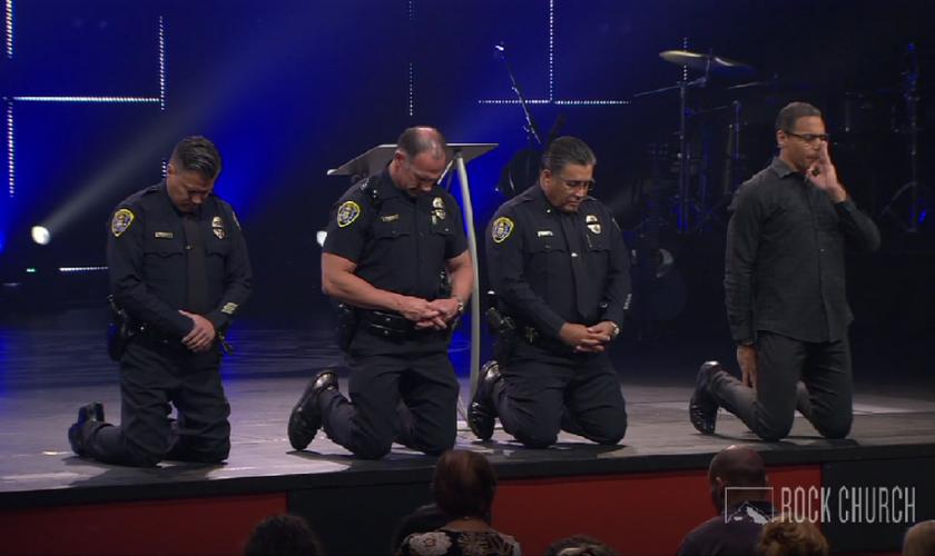 Pastor Miles McPherson ora com policiais durante culto em sua igreja. (Foto: SDROCK)