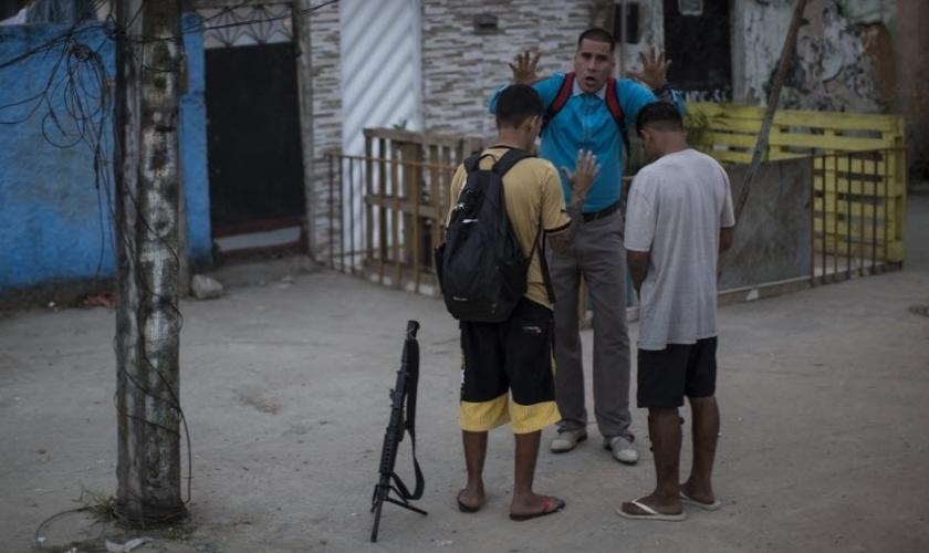 Dois jovens traficantes deixaram um fuzil de lado para receber uma oração do pastor Nilton. (Foto: Felipe Dana/AP)