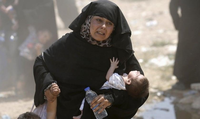 Refugiada síria foge do terror do Estado Islâmico com os filhos. (Foto: Reuters)