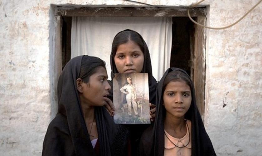Filhas de Asia Bibi mostram foto da mãe, do lado de fora de sua casa. (Foto: Reuters)