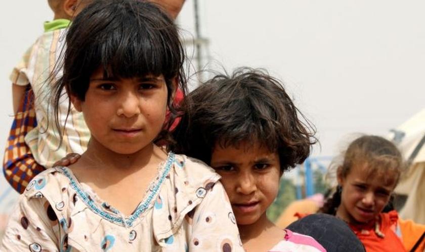 Crianças refugiadas, que fugiram da violência do Estado Islâmico, posam para um fotógrafo em um campo de refugiados na área de Makhmour, perto de Mosul, Iraque. (Foto: Reuters)