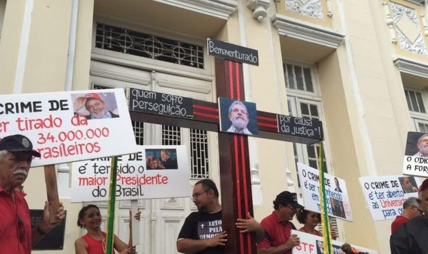 Militante segura cruz com foto de Lula ao centro, em frente à Câmara Municipal do Recife. (Foto: UOL)