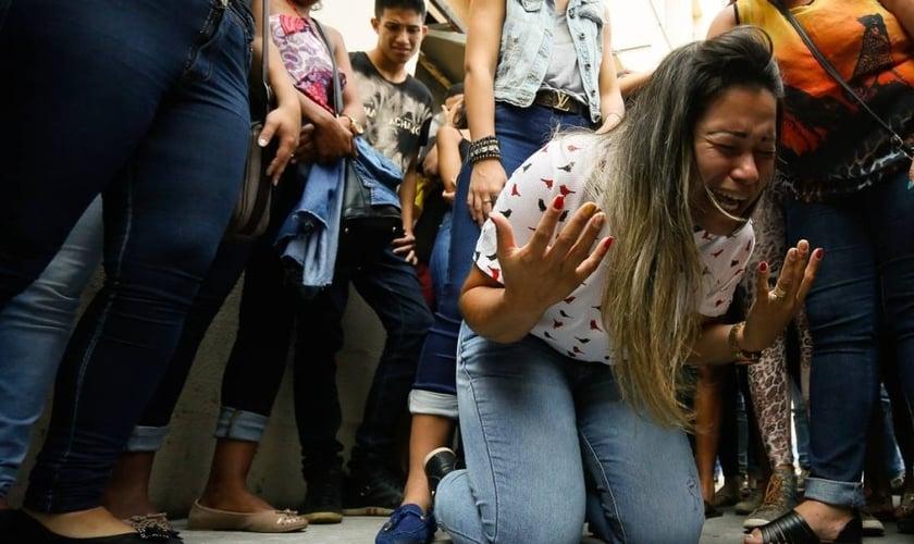 Vanessa da Silva, mãe de Renan, se ajoelha após direção do hospital decidir manter jovem ligado a aparelhos. (Foto: Pablo Jacob/Agência O Globo)