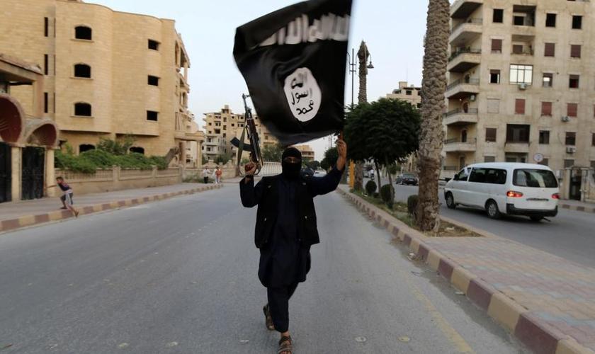 Militante do Estado Islâmico exibe bandeira da organização terrorista. (Foto: Reuters)