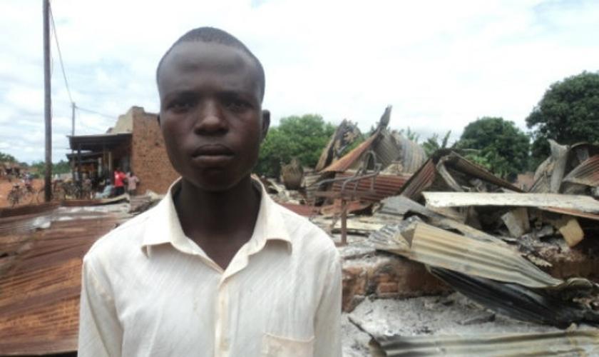 Homem em frente aos restos de sua pequena empresa, em Uganda. (Foto: Reprodução/Portas Abertas)