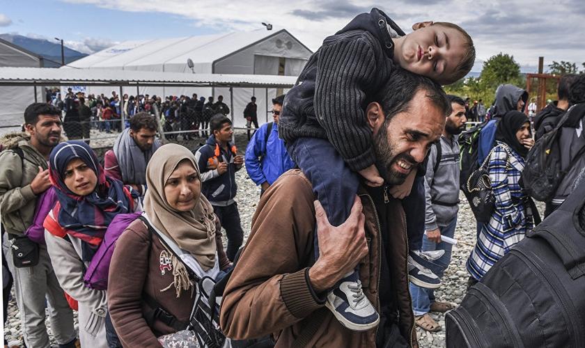 Refugiados do Oriente Médio aguardam em fila, após chegaram à Europa. (Foto: AFP)