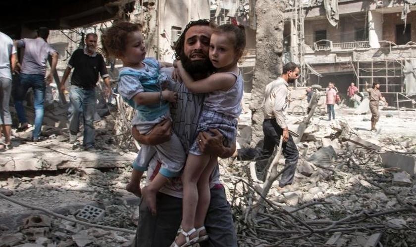 Pai carrega seus filhos em meio a conflito em Aleppo. (Foto: International Business Times)