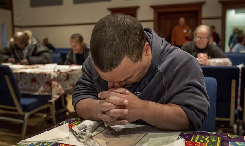 Homem ora durante sessão de artesanato na Missão Bethesda, Pensilvânia. (Foto: PennLive)