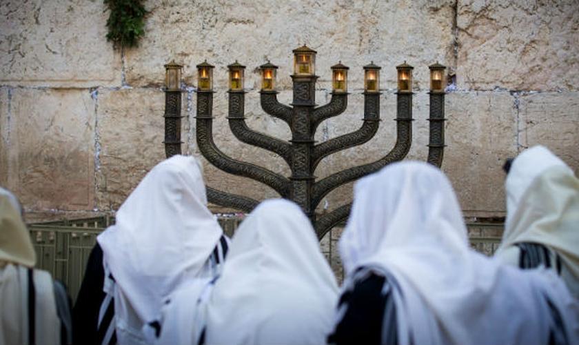 Judeus oram em frente a um menorá no Muro das Lamentações. (Foto: Miriam Alster/Flash90)