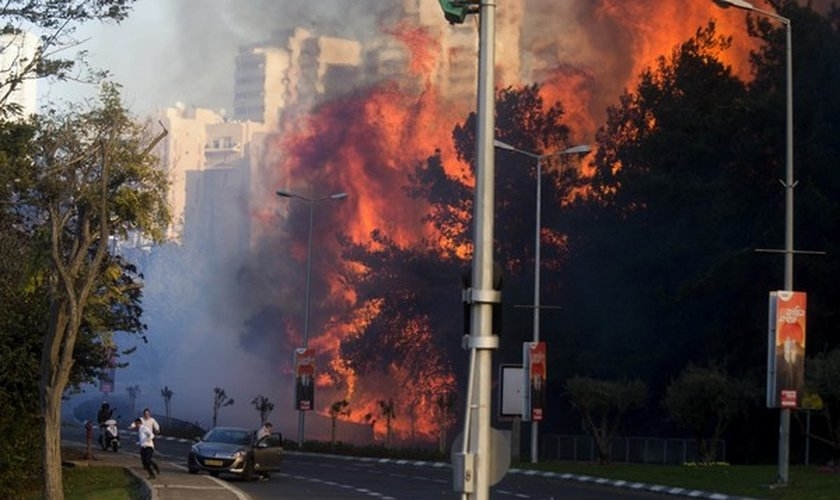 Pessoas correm em rua de Haifa, em Israel, enquanto incêndio avança nesta quinta-feira (24). (Foto: AP Photo/Ariel Schalit)