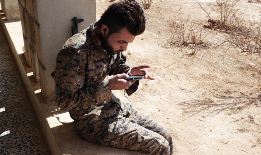 Soldado curdo escuta Bíblia em áudio com mensagens em sua própria língua. (Foto: Audio Scripture Ministries)