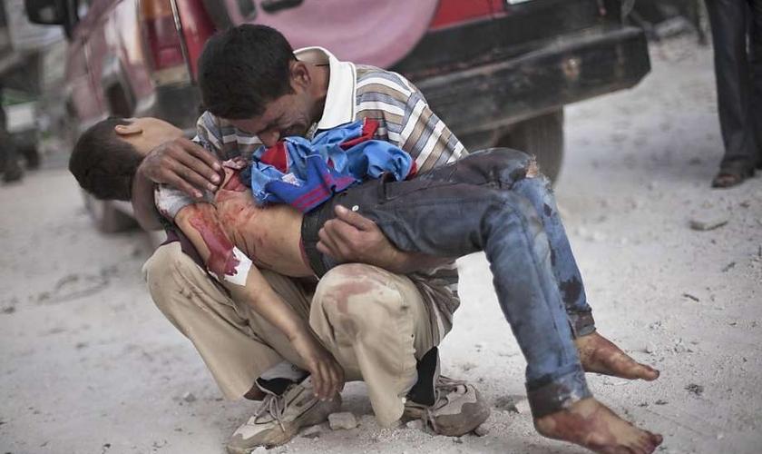 Pai segura seu filho morto em Aleppo, na Síria, depois de um atentado suicida. (Foto: Manu Brabo/Associated Press)