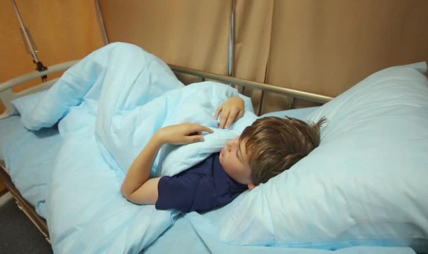 Garoto deitado em uma cama de hospital. (Foto: Shutterstock)