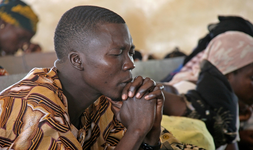Cristão nigeriano orando durante culto. (Foto: Crossmap)