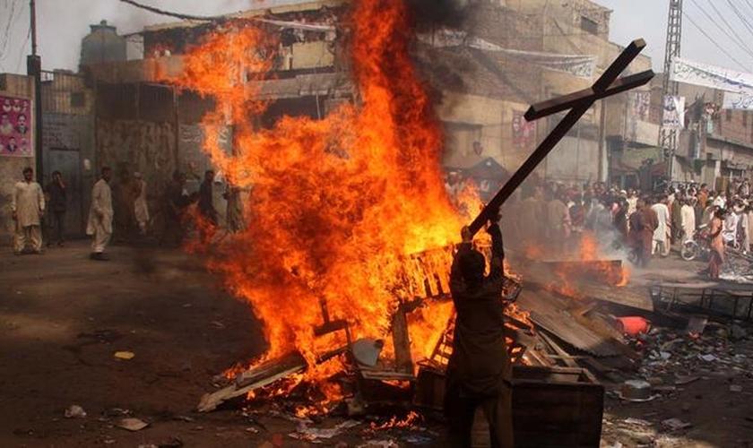 Manifestante queima uma cruz durante um protesto em Lahore, no Paquistão. (Foto: Adrees Hassain/Reuters)