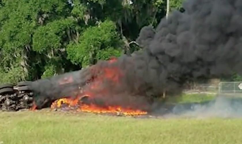 O caminhão capotou na grama da rodovia e foi tomado pelas chamas. (Foto: Reprodução/News 6)