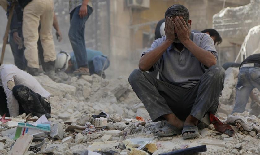 Homem chora em meio a destroços, após bombardeio em Aleppo. (Foto: Reuters)